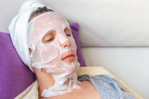 化粧マスクの女性はソファのクローズアップに横たわっています