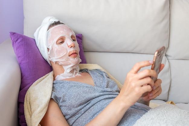 電話で化粧マスクの女性はソファのクローズアップに横たわっています