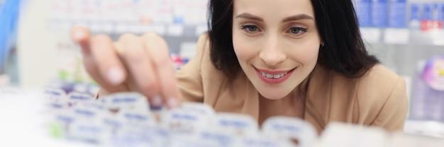 化粧品店の女性がスキンケア商品を手に取る