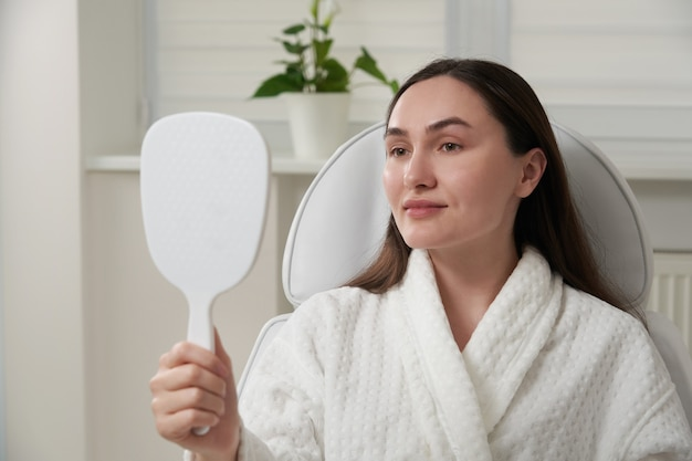Женщина в косметологическом салоне довольна результатом косметической процедуры