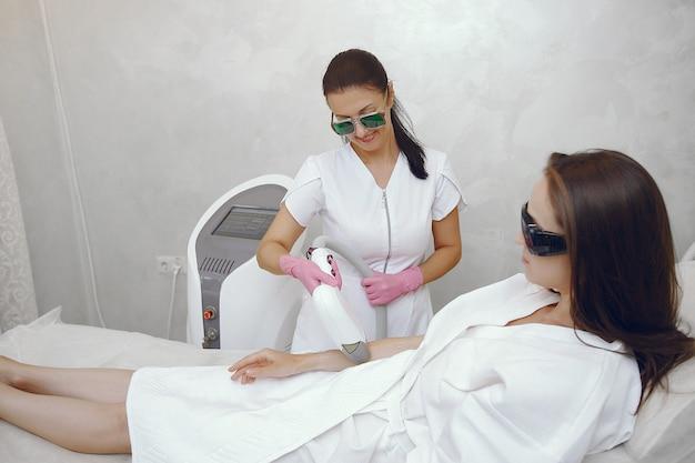 Женщина в косметологической студии по лазерной эпиляции