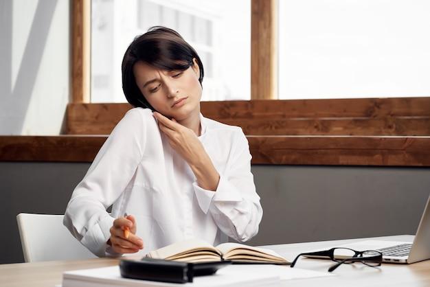 노트북 문서 앞의 의상을 입은 여성은 직업적인 밝은 배경을 문서화합니다.