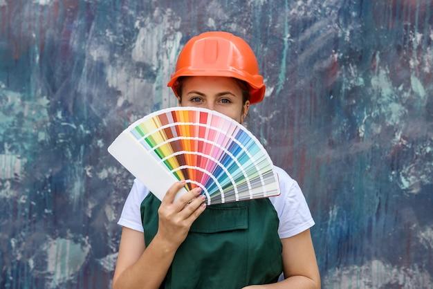 Женщина в комбинезоне позирует с образцом цвета в веере на красочной стене