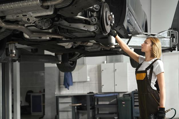 Женщина в комбинезоне чинит тормозные диски поднятой машины.