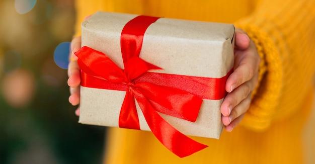 Женщина в уютном желтом вязаном свитере дарит рождественские поделки из подарочных коробок с красной лентой ...