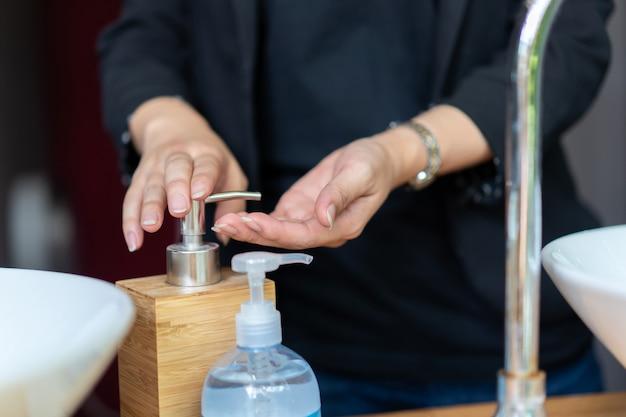 검은 색 정장을 입은 여자는 싱크대 옆에 그녀의 손에 비누를 씻고 있습니다.