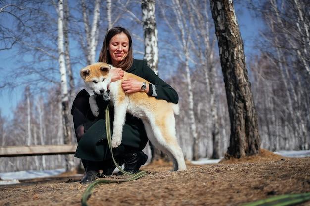 暗いコートを着た女性が秋の公園で長い緑のひもで秋田犬の子犬を抱きしめます