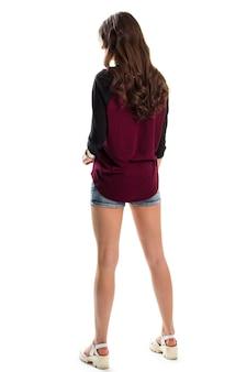 濃い色のトップの女性。白い靴とジーンズのショートパンツ。トレンディなデザインと高品質の素材。見栄えの良いモデル。