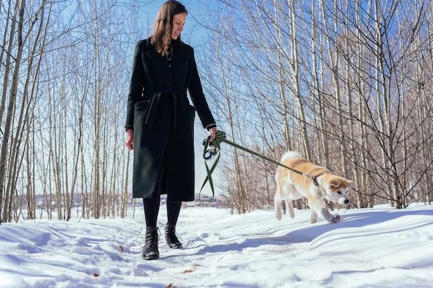 濃い緑色のコートを着た女性が、雪に覆われた路地で緑のひもにつないで秋田犬の子犬を歩く
