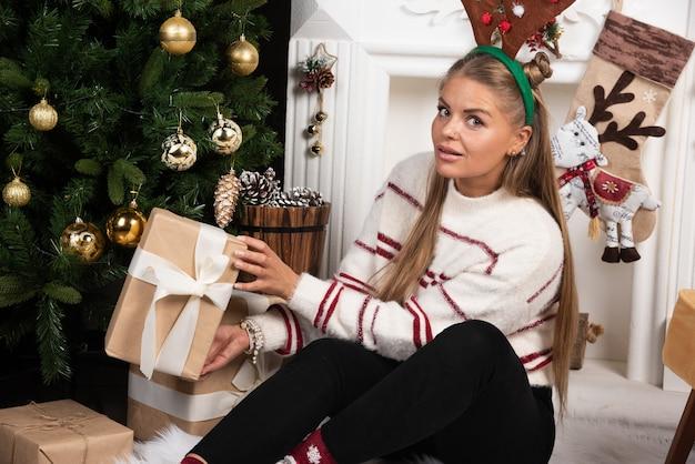 Женщина в оленьих ушах показывает подарок возле елки.