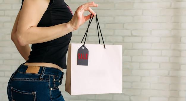Женщина в джинсовой ткани держит в руке бумажный пакет с биркой у белой кирпичной стены в торговом центре