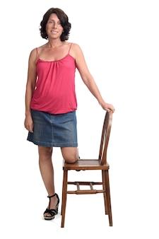 Женщина в джинсовой юбке играет со стулом на белом фоне