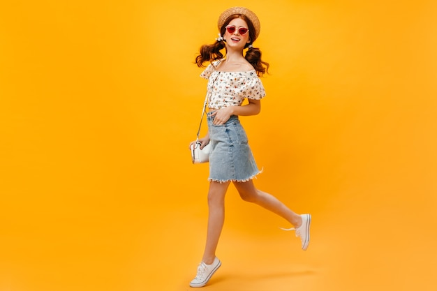 Женщина в джинсовой юбке, белой футболке и канотье прыгает на оранжевом фоне. женщина в солнцезащитных очках улыбается.