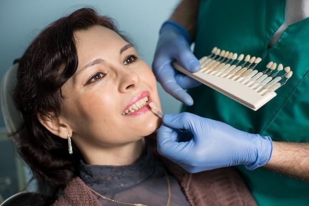 歯科医院の女性。歯科医は歯の色をチェックして選択し、治療のプロセスを作ります