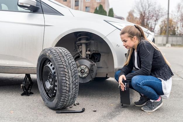 Женщина в отчаянии смотрит на запасное колесо для автомобиля