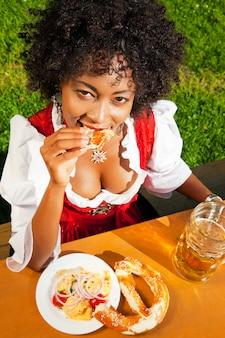 プレッツェルを食べるギャザースカートの女性