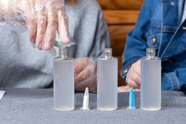 테스트 튜브에서 화학 원소를 테이블에 병에 붓는 일회용 장갑에 여자.