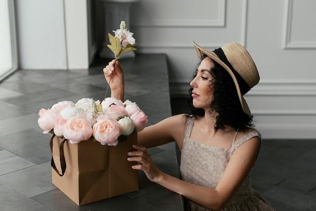 ドレスと帽子の女性は装飾的な花の小枝を挿入します