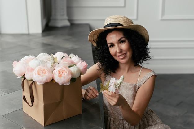 花の白とピンクの花束の横にドレスと麦わら帽子の女性