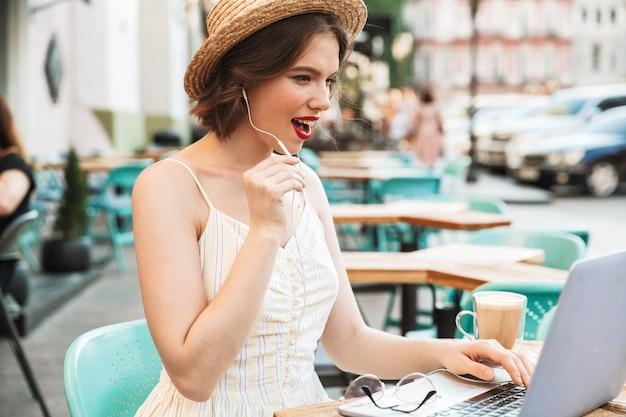 ビデオ通話で話しているドレスと麦わら帽子の女性