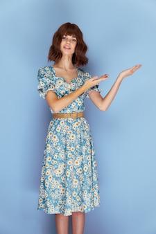 ドレスを着た女性先を見据えて手でジェスチャー