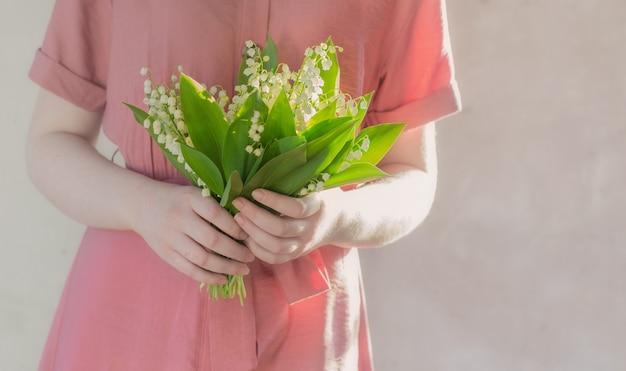 배경 오래 된 벽에 릴리 밸리의 꽃다발을 들고 드레스 여자