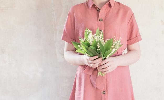 오래 된 벽에 은방울꽃의 꽃다발을 들고 드레스 여자