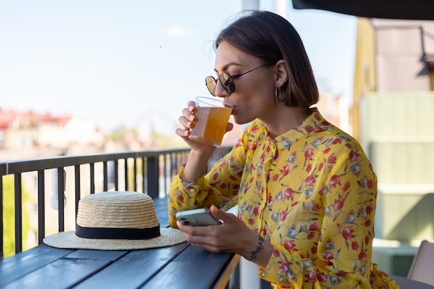 Женщина в платье в летнем кафе, наслаждаясь прохладным бокалом пива чайного гриба