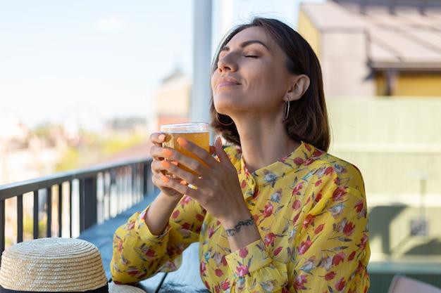 クールな紅茶キノコビールを楽しむ夏のカフェでドレスを着た女性