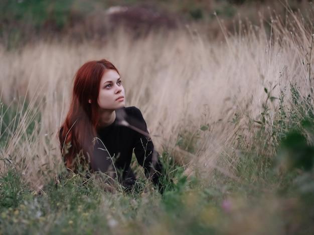 ドレスを着た女性は草の自然の自由に横たわっています