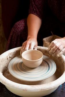 Женщина в лепке платья из глины на гончарном круге