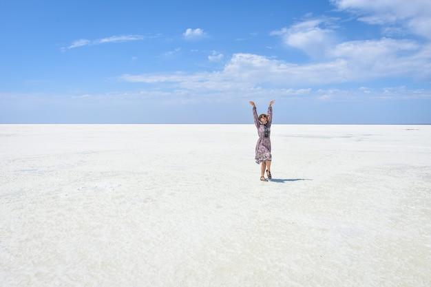 白い塩湖の上のドレスの女性白い塩湖の上の女性の肖像画白い塩湖の上の帽子と眼鏡の女性