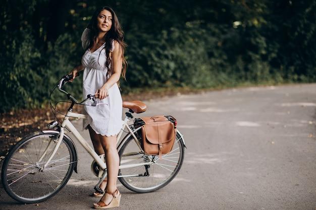 Женщина в платье, езда на велосипеде в парке
