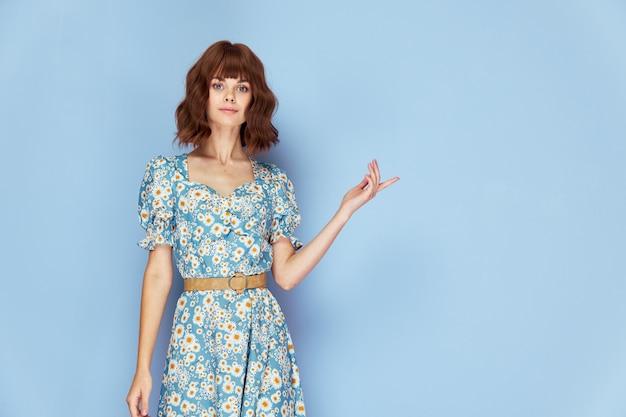 ドレスを着た女性笑顔の手のジェスチャーコピースペース短い髪の青い背景