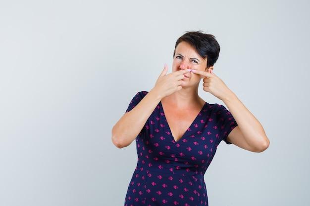 Женщина в платье, сжимая прыщ на щеке