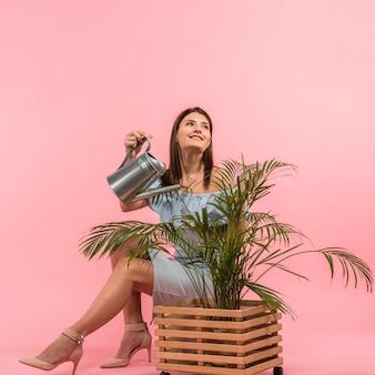 ポットの植物の水まきのドレスの女