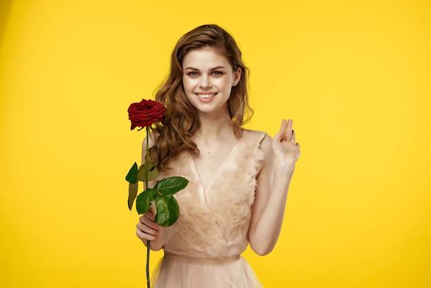 Женщина в платье с розовым цветком очарование желтом фоне