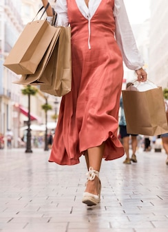 路上で買い物袋とドレスの女性