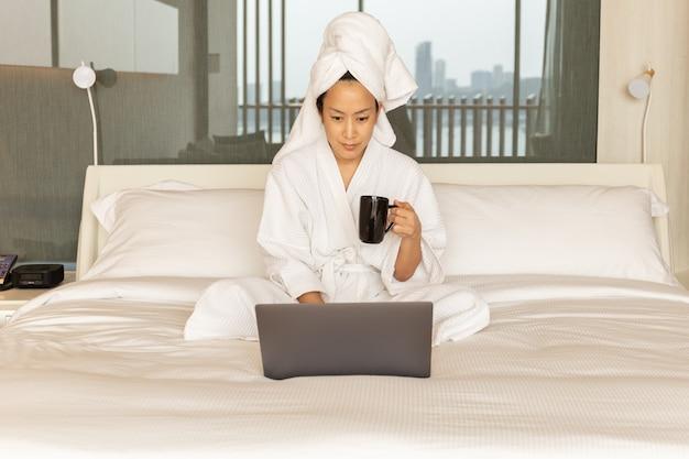 Женщина в халате и полотенце на голове сидит на кровати, рука кофе работает на ноутбуке.