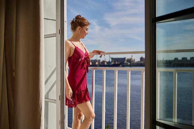 드레싱 가운을 입은 여성이 더운 여름날 발코니에 서 있다