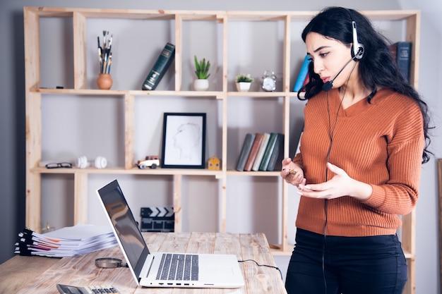 Женщина в наушниках учится онлайн на ноутбуке, делает заметки