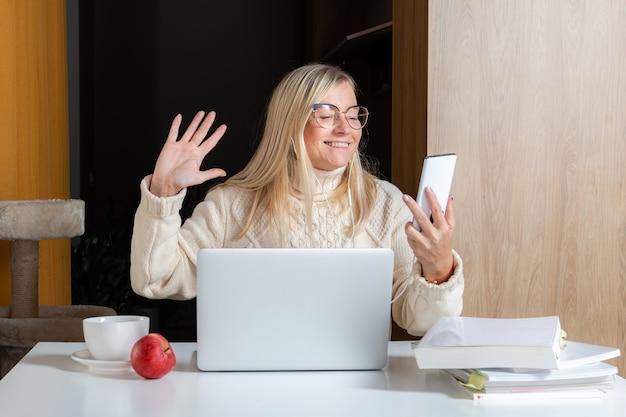 집 부엌에서 노트북으로 작업하는 동안 핸드폰을 사용하는 이어폰에 여자, 온라인 라이프 스타일 작업