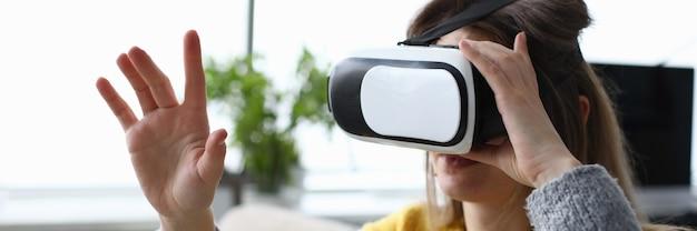 電子プロのバーチャルリアリティメガネの女性がシミュレータービデオを見る。