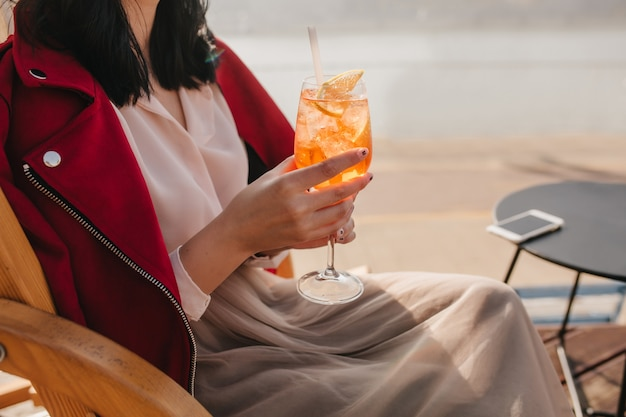 屋外カフェでオレンジ色の飲み物を飲むエレガントなベージュのスカートの女性