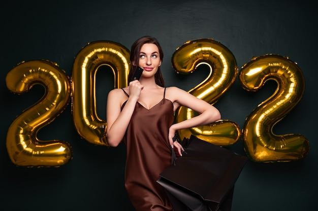 Женщина в элегантном платье держит кредитную карту и сумки для покупок на черном фоне с цифрами на воздушном шаре ...