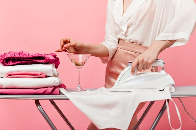 Женщина в элегантном наряде размешивает мартини в стакане и гладит одежду