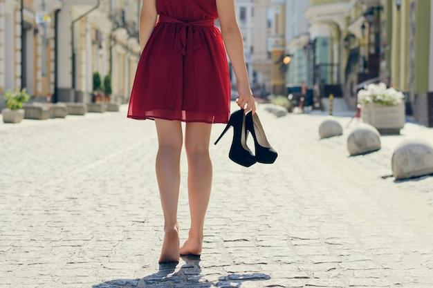 Женщина в элегантном красном платье, держащая в руках туфли на высоком каблуке и идущая босиком, возвращается домой после вечеринки утром; вид со спины; город на заднем плане