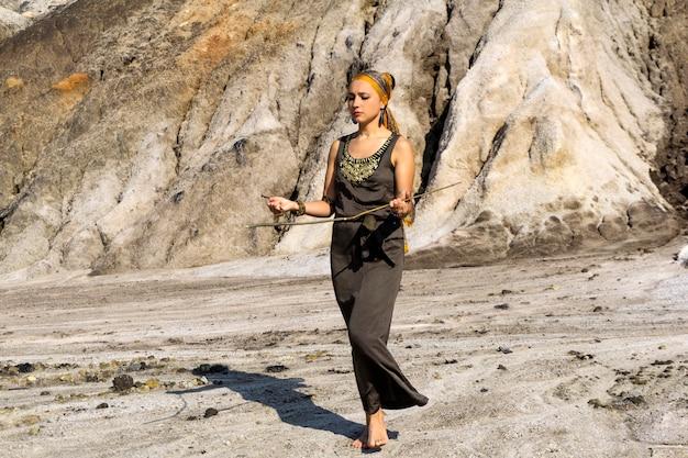 동양인 복장을 한 여성이 측량법으로 사막 지역에서 물을 찾고 있다