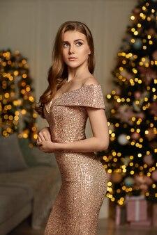 クリスマスツリーの上のイブニングドレスの女性