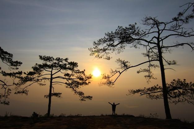 Женщина в вечернем свете с горы и туман на фоне.